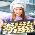 Little girl holding a baking sheet of cookies cute Stock Images