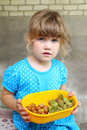 Little girl holding bowl with hazelnuts in blue dress Royalty Free Stock Images