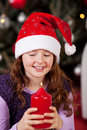 Little girl holding the christmas candle joyful wearing a festive red santa hat carefully burning large red Stock Image
