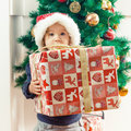 Little girl holding a christmas gift cute with santa hat at home Royalty Free Stock Image
