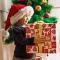 Little girl holding a christmas gift cute with santa hat at home Royalty Free Stock Photography