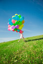 Little girl holding colorful balloons child playing on a green happy meadow smiling kid Stock Photos