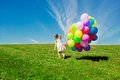 Little girl holding colorful balloons. Child playing on a green Royalty Free Stock Photo