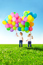 Little girl holding colorful balloons child playing on a green happy meadow smiling kid Stock Images