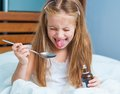 Little girl holding a cough syrup bottle dissatisfied with influenza in bed Stock Photo