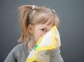 Little girl holding handkerchief grey background Stock Photo