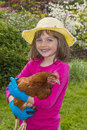Little girl holding a hen in the garden Stock Images