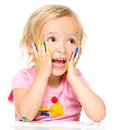 Little girl is holding her face in astonishment while playing with paints isolated over white Royalty Free Stock Images