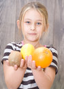 Little girl holding kiwi lemon and orange on a background of wooden boards Stock Photos