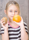 Little girl holding kiwi and orange on a background of wooden planks Stock Photo