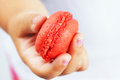 Little girl holding macaroon s hand a red Royalty Free Stock Images