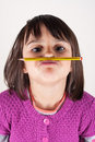 Little girl holding a pencil like a mustache naughty concept of education Stock Photo