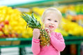 Little girl holding a pineapple in a food store Royalty Free Stock Photo