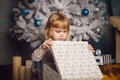 Little girl holding present near the christmas tree Royalty Free Stock Photo