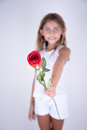Little Girl holding a red flower offering for you Royalty Free Stock Photo