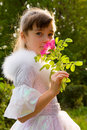 Little girl holding rose flower to her face Royalty Free Stock Image