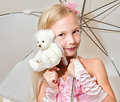 Little girl holding umbrella and wedding bear teddy is wearing pink dress Royalty Free Stock Images