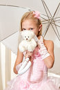 Little girl holding umbrella and wedding teddy bear is wearing pink dress Stock Photos