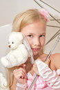 Little girl holding umbrella and wedding teddy bear is wearing pink dress Royalty Free Stock Image