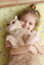 The little girl hugging the cat lying on a mattress on the floor the girl smiles he tries to escape Royalty Free Stock Photography