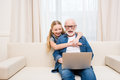 Little girl hugging happy grandfather using laptop at home Royalty Free Stock Photo