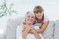 Little girl hugging her grandmother sitting on the couch Royalty Free Stock Images