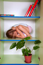 Little girl hugging a toy and hiding in a closet Stock Images