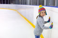 Little girl ice skating adorable wearing jeans warm sweater and colorful hat on rink Royalty Free Stock Images