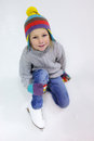 Little girl ice skating adorable wearing jeans warm sweater and colorful hat on rink Royalty Free Stock Image