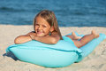 Little girl with inflatable mattress or raft on the beach sunbathing Stock Photo