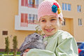 Little girl in jacket stands holding rabbit smiling greenish and knitted hat her hands Stock Photos