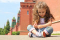 Little girl in jeans sits near old brick wall on the asphalt and towers and tying shoelaces Stock Photography