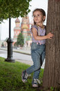 Little girl in jeans standing next to a tree with suspenders Stock Image