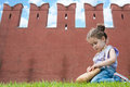 Little girl in jeans with straw bag sits on the grass near old brick wall Royalty Free Stock Photography