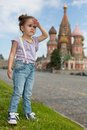 Little girl in jeans with suspenders near the saint basils cathedral look into distance Stock Photos