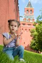 Little girl in jeans with suspenders sitting on the grass near old brick wall and tower Stock Photos