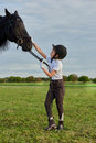 Little girl jockey communicating with her black horse in professional outfit Royalty Free Stock Photo