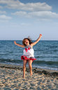 Little girl jumping on the beach happy Royalty Free Stock Photography