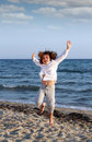 Little girl jumping on beach summer scene happy Royalty Free Stock Image