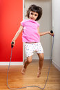 Little girl jumping rope at home in the living room Royalty Free Stock Image