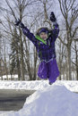 Little girl jumps off snow pile a in the air the top of a she is smiling from ear to ear and wearing a bright purple and green Royalty Free Stock Image