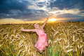 Little girl jumps in a wheat field. Stock Photo