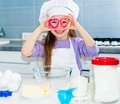 Little girl and keeps cookie cutters cute has fun near eyes Stock Photo