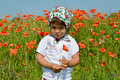 The little girl keeps red poppy in a poppy field Royalty Free Stock Photo