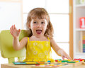 Little girl kid playing with logical toys. Child sorting and arranging colors and forms. Royalty Free Stock Photo