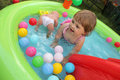 Little girl in kids pool cute having fun the inflatable the garden Stock Images