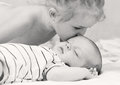 Little girl kisses a sleeping baby brother black and white Royalty Free Stock Image