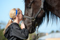 Little girl kissing her horse outdoor profile portrait of a cute caucasian with a long blond ponytail purebred friesian with much Royalty Free Stock Photography