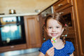Little girl in the kitchen smiling eating lollipop cute with two braids spaghetti Stock Photos