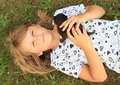 Little girl with a kitty smiling kid lying on meadow small black on chest Royalty Free Stock Photography